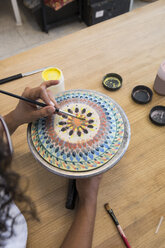 Woman painting a ceramic plate with a brush - ABZF01252