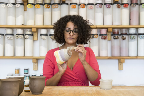 Woman painting a ceramic mug with a brush in her workshop - ABZF01255