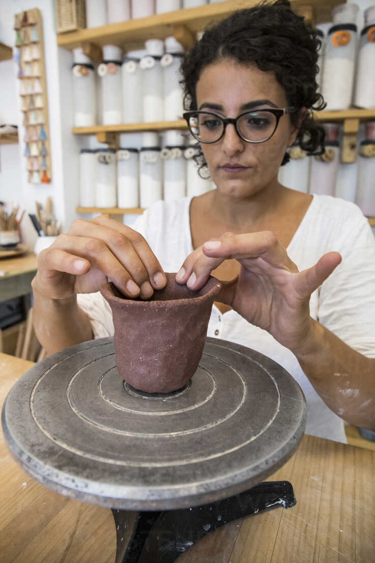 Woman sculpting a cup with clay in a ceramic workshop - ABZF01261 - Andrés Benitez/Westend61