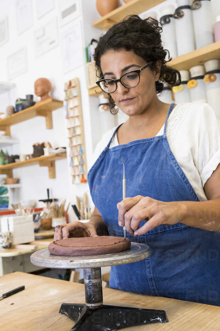 Woman working with clay in a ceramics workshop - ABZF01264 - Andrés Benitez/Westend61