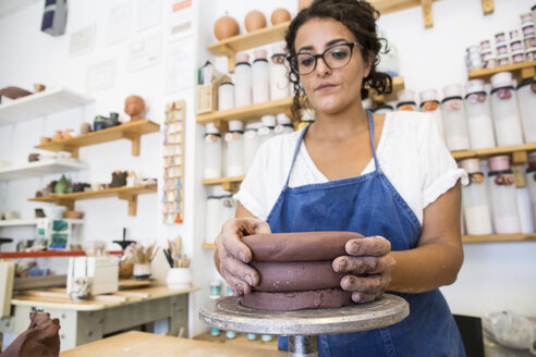 Woman working with clay in a ceramics workshop - ABZF01267
