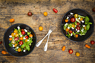 Two bowls of leaf salad with goat cream cheese and tomatoes on wood - LVF05339