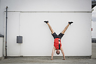Man doing handstand against wall - ASCF00656