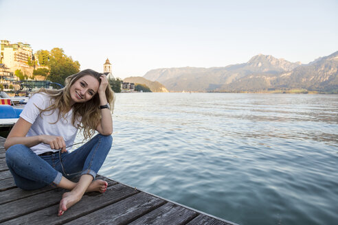 Austria, Sankt Wolfgang, smiling woman sitting on jetty at lake - JUNF00628