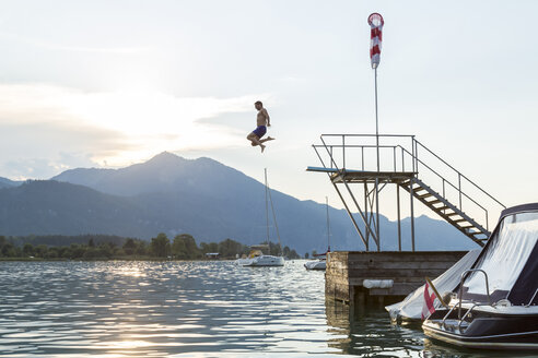 Austria, Sankt Wolfgang, man jumping from platform into lake - JUNF00643