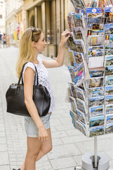 Austria, Salzburg, tourist choosing post cards - JUNF00646