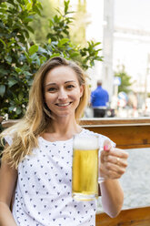 Portrait of happy woman with beer mug in a street restaurant - JUNF00652