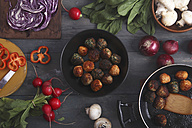 Meatballs in a pan and various vegetables on wood - RTBF00391