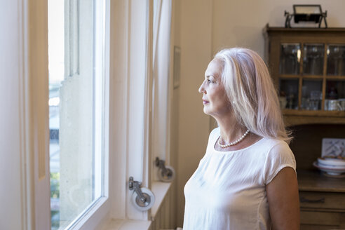 Mature woman looking through window at home - JUNF00664