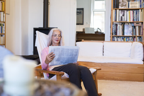 Mature woman sitting in armchair at home reading newspaper - JUNF00670