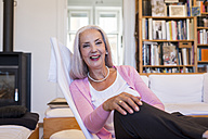 Laughing woman sitting in armchair at home - JUNF00673