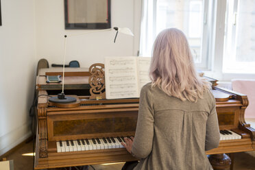 Back view of woman playing piano at home - JUNF00676