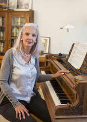 Portrait of woman with piano at home - JUNF00679