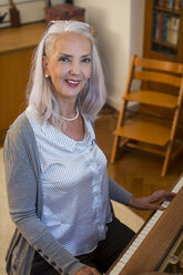 Portrait of smiling woman playing piano at home - JUNF00682