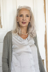 Portrait of mature woman in front of door - JUNF00685