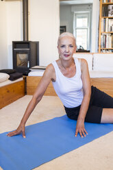 Portrait of woman sitting on gym mat in living room - JUNF00697