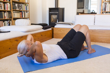 Woman exercising on gym mat in living room - JUNF00700