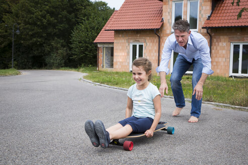 Father and daughter longboarding in garden - JTLF00118