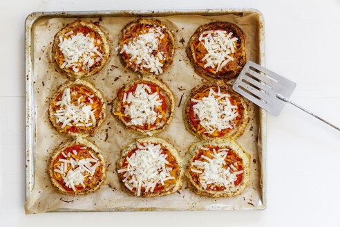 Homemade glutenfree mini pizzas with cauliflower and pumpkin on baking tray - EVGF03074