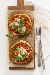 Two homemade glutenfree mini pizzas with cauliflower, pumpkin and rocket on wooden board - EVGF03077