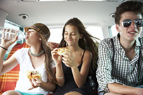 Three teenage friends having a snack in car - FSF00531