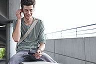 Smiling teenage boy with cell phone and earbuds outdoors - FSF00537