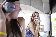 Two teenage girls using tin can phone - FSF00543