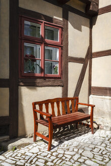 Germany, Lower Saxony, Hildesheim, empty wooden bench in front of half-timbered house - EVGF03086