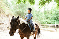 Little boy riding horse at riding school - VABF00791