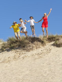 Family jumping from sand dune - LAF01763