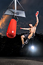 Kickboxer exercising with punch bag - STSF01103