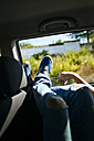 Legs of a man leaning out of car window - KIJF00785