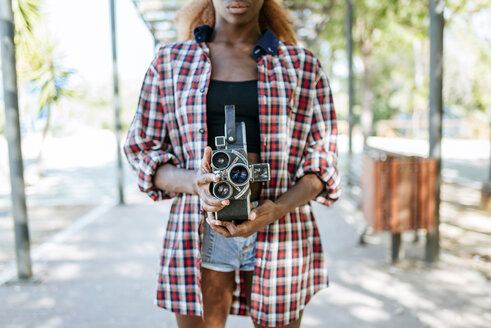 Young woman holding an old-fashioned camera - KIJF00812