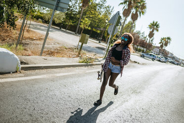 Young woman holding skateboard running on a street - KIJF00815