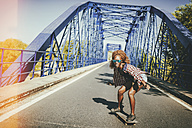 Young woman on skateboard on a bridge - KIJF00818