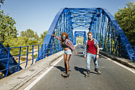 Young couple with inline skates and skateboard riding on a bridge - KIJF00821
