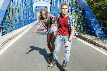 Young couple with inline skates and skateboard riding on a bridge - KIJF00824