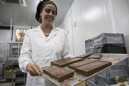 Woman holding a tray with chocolate nougat in a chocolate factory - ABZF01296