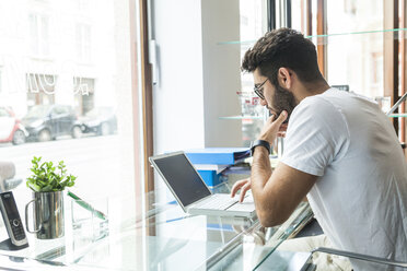 Young man working with laptop at desk in a modern office - TCF05106