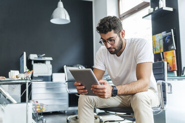 Young man looking at tablet in a modern office - TCF05109