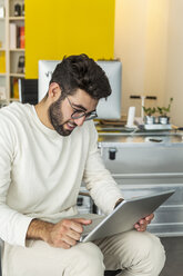 Young man with laptop in a modern office - TCF05115