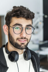 Portrait of smiling man with glasses and headphones - TCF05124