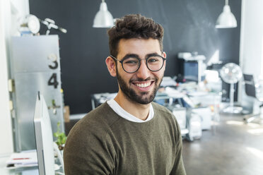 Portrait of smiling man with glasses in a modern office - TCF05127