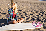 Spain, Tenerife, young blonde surfer sitting on the beach - SIPF00871
