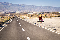 Spain, Tenerife, blond young skater walking on road - SIPF00895