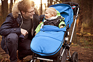 Father smiling at son in buggy in forest - MFF03363