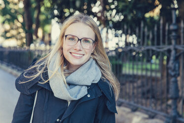 Portrait of smiling young woman with glasses and scarf - MFF03381