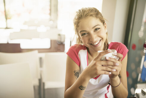Smiling young woman in a cafe drinking coffee - JASF01142