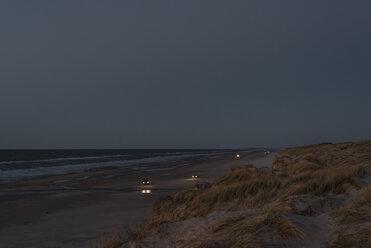 Denmark, Blokhus, cars on the beach at dusk - MJF02007