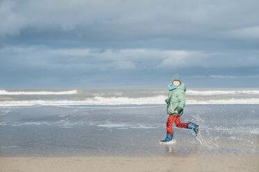 Denmark, Skagen, boy in winter clothes running on beach - MJF02013